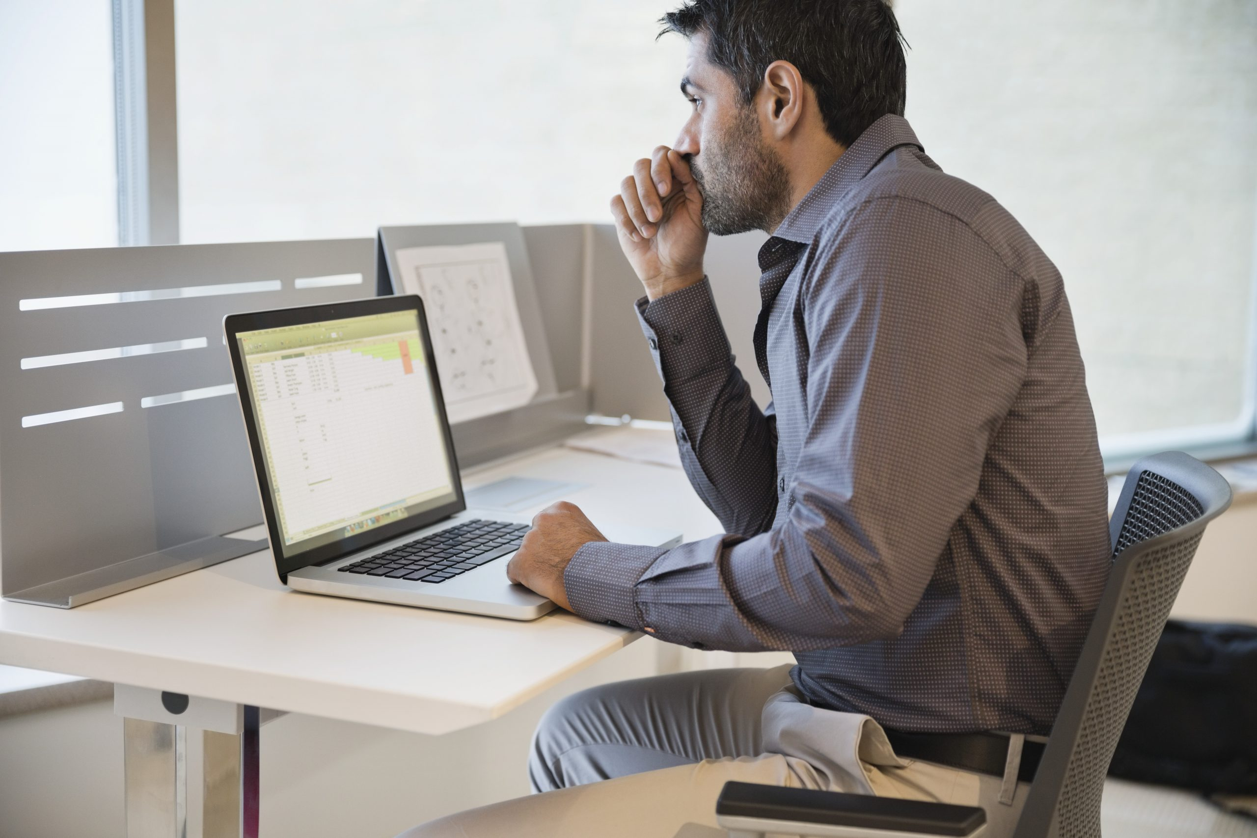 Thoughtful businessman with laptop on office desk
